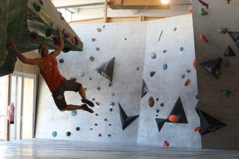 Ein Mann klettert an der Wand entlang.