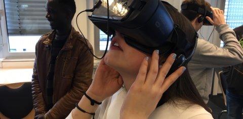 Ein Mädchen schaut vor weiteren Personen durch eine VR-Brille