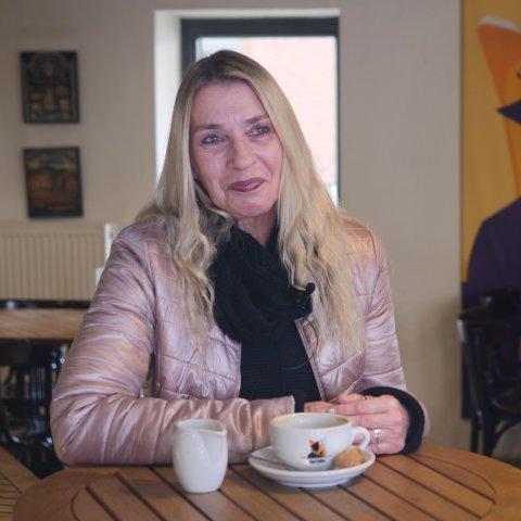 """Eine Frau sitzt im Café """"Lloyd Caffee"""" an einem Tisch, auf dem eine Tasse und ein Milchkännchen stehen. Im Hintergrund stehen weitere Tische und Stühle. An der Wand hängt ein Poster des Cafés."""