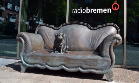 Das Bronze-Replik des Loriot Sofas inklusive des Mops vor dem Radio Bremen Gebäude.