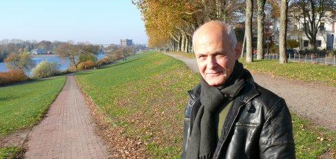 Mehmet Altun lächelt in die Kamera. Er steht auf einer Grünfläche.