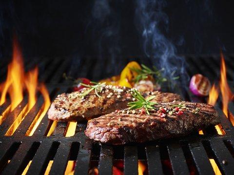 Gegrilltes Steak auf einem Rost, im Hintergrund Feuer.