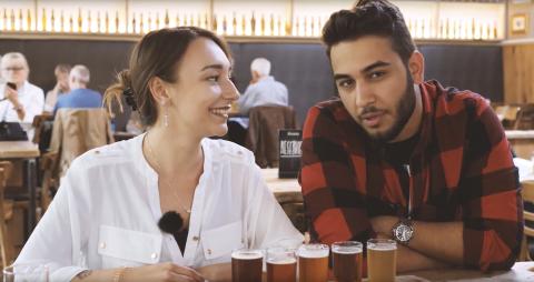 Eine junge Frau und ein junger Mann sitzen an einem Tisch. Vor ihnen steht eine Reihe mit kleinen, gefüllten Biergläsern.