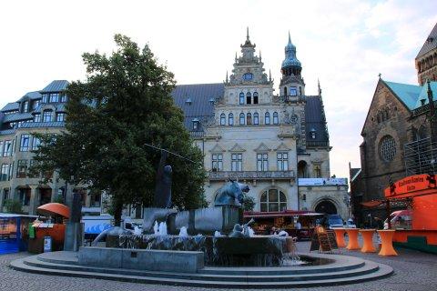 Im Hintergrund liegt das historische Gebäude der Bremer Bank. Davor reihen sich einige Marktstände sowie der Neptunbrunnen am Marktplatz.