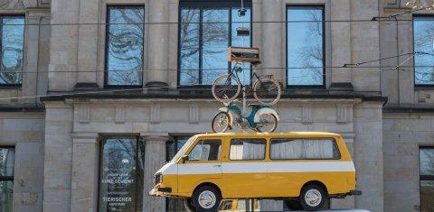 Autos und Fahrräder sind übereinander gestapelt und stehen vor der Kunsthalle