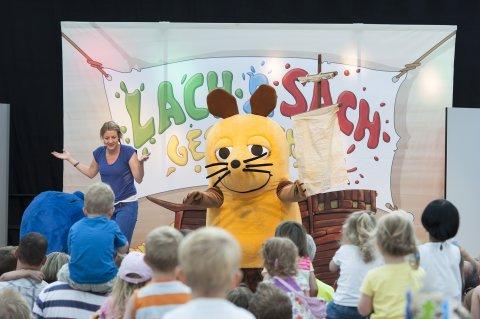 Die Maus der Sendung mit der Maus tritt auf einer Bühne vor vielen Kindern auf