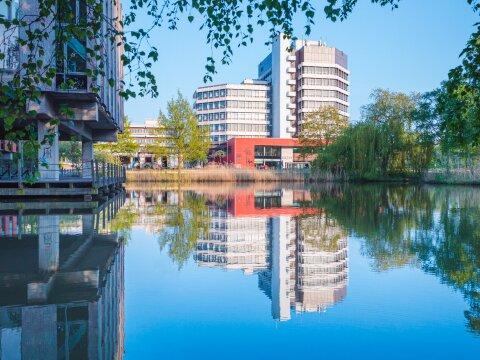 Das Uni Bremen-Gebäude MZH. Im Vordergrund steht der Mensasee. Das Gebäude spiegelt sich im See.