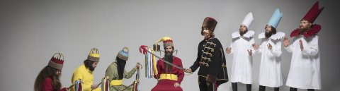 """Zu sehen sind acht kostümierte Männer. Das Bild trägt den Namen """"Der Traum der Könige""""."""