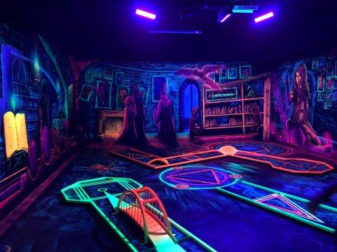 Ein Raum der Minigolf Helden in Findorff. Die Wände sind in bunter Neonfarbe bemalt. Es sind Hexen und Zauberer zu sehen.