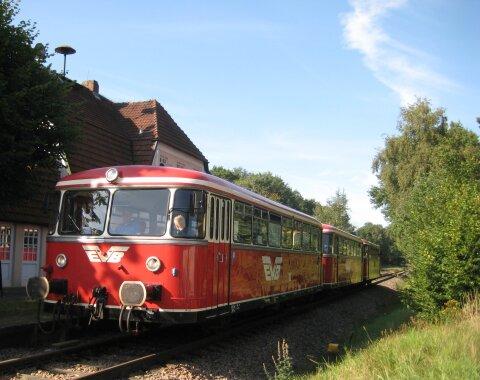 Ein kleiner, alter Zug hält an einem Bahngleis.