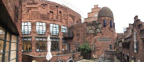 """Die rotbraune Außenfassade der Museen Böttcherstraße mit Terrasse und Kuppel. Auf der rechten Bildseite ist ein kleiner Teil der Gasse """"Böttcherstraße"""" zu erkennen."""