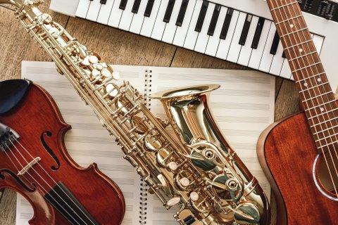 Geige, Saxophon und Gitarre angeschnitten auf Notenpapier liegend