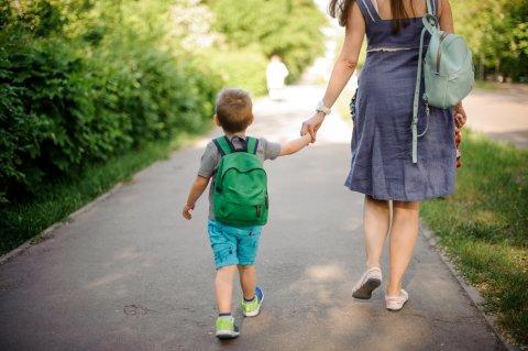 Ein kleiner Junge mit Rucksack läuft Hand in Hand mit seiner Mutter auf einem Weg im Park.
