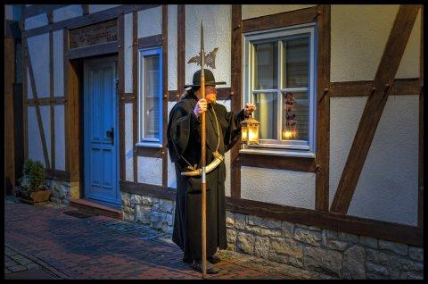 Ein als Nachtwächter verkleideter Stadtführer vor einem alten Fachwerkhaus