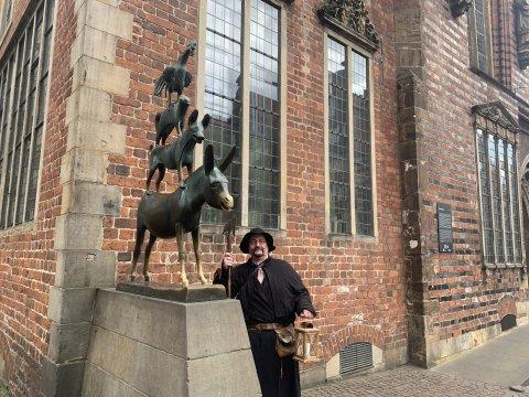 Der Bremer Nachtwächter steht in einer Kutte gekleidet und mit einer Laterne in der Hand vor den Bremer Stadtmusikanten.