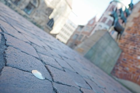 Ein Nagel im Boden steht im Fokus, im Hintergrund sieht man verschwommen die Bremer Stadtmusikanten.