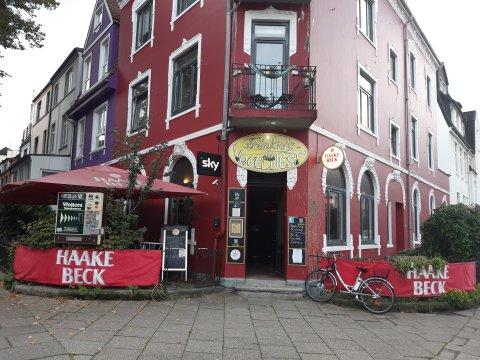 """Die Kneipe """"Fränkie's Vogelnest"""" von außen. Die Fassade ist dunkelrot angestrichen. Rechts und links ist eine Verkleidung an dem Zaun, auf dem """"Haake Beck"""" steht. Über der offenen Tür hängt ein gelbes Schild auf dem mit weißer Schrift """"Fränkie's Vogelnest"""" steht."""