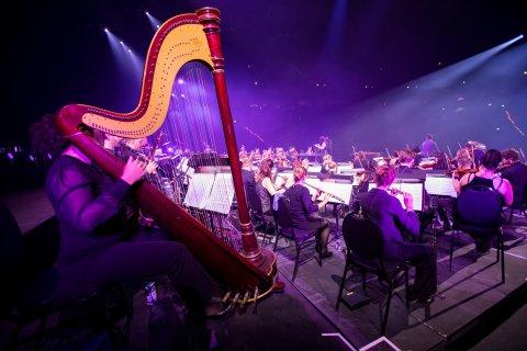 Eine große Band mit verschiedenen Musikinstrumenten, unter anderem ein Chello, Querflöten und Geigen.