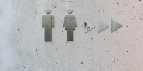 Ein Wegweiser weist die Toiletten aus