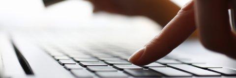 Ein Finger tippt auf eine Tastatur.