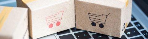 Tastatur eines Laptop mit kleinen Kartonwürfeln, auf denen Einkaufswagen abgebildet sind.