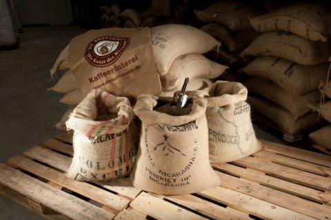 Drei Säcke, gefüllt mit Kaffeebohnen, stehen auf einer Palette.
