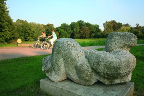 Im Vordergrund eine abstrakte Plastik, im Hintergrund zwei Radfahrer im Oslebshauser Park.