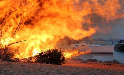 Ein Osterfeuer am Strand eines Flusses.