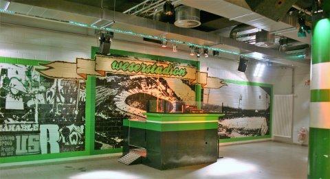 Man sieht den Ostkurvensaal im Weserstadion von innen. Zu sehen ist eine Bar vor einem grün-schwarzen Wandbild vom Weserstadion.