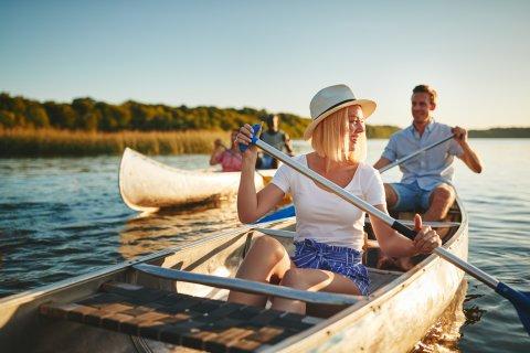 Zwei Ruderboote auf einem Fluss, jeweils gesteuert von einer Frau und einem Mann.