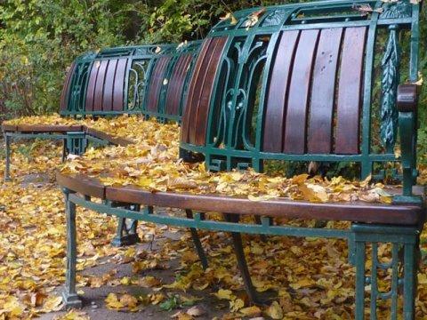 Jugendstil-Parkbank mit Herbstlaub