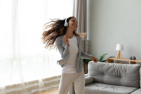 Eine junge Frau tanzt mit Kopfhörern auf in ihrem Wohnzimmer