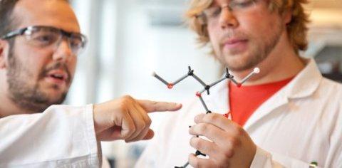 Zwei Männer in Schutzanzügen betrachten ein Modell einer chemischen Verbindung