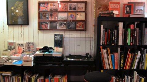 Ein Schallplattenspieler und Kopfhörer umgeben von Büchern und Schallplatten.