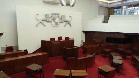 Ein großer Saal in der Bremischen Bürgerschaft mit Holzpult, rotem Teppich, Holztischen und roten Stühlen.