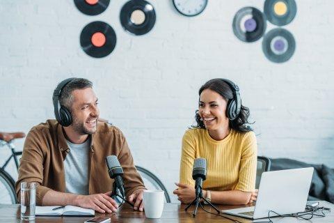 Zwei Personen unterhalten sich und haben Kopfhörer auf. Vor ihnen zwei Mikrofone.