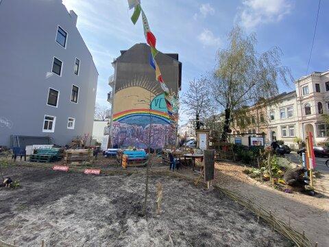 Zu sehen ist der Stadtgarten im Viertel. In dem Beet ist bisher noch Erde zu sehen, da die Pflanzen noch nicht gewachsen sind.