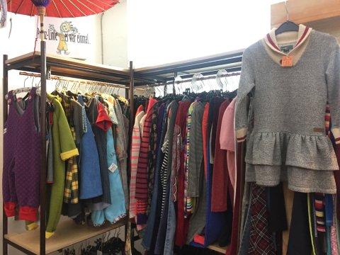 Bunte Kinderkleidung in verschiedenen Größen hängt an Stangen