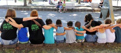 Kinder sitzen auf einer Mauer und haben einander die Arme um die Schultern gelegt.