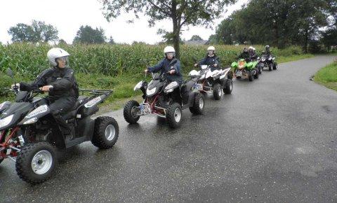 Sieben Personen beim Quad-Fahren auf verregneter Landstraße.