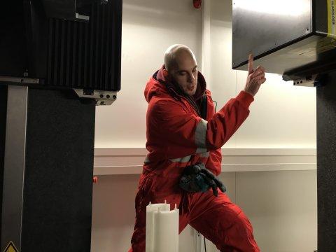 Ein Mann in rotem Overall steht zwischen zwei Röntgengeräten