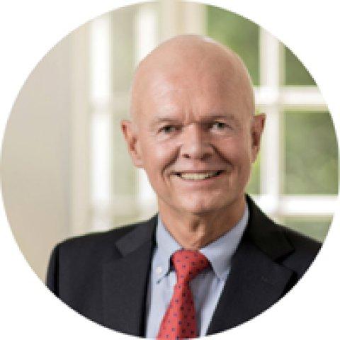 Portrait eines älteren Herrn mit Glatze im schwarzen Anzug mit roter Krawatte