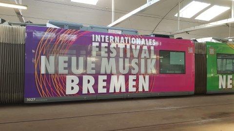 Eine Straßenbahn mit Werbeschriftzügen in einem Depot.