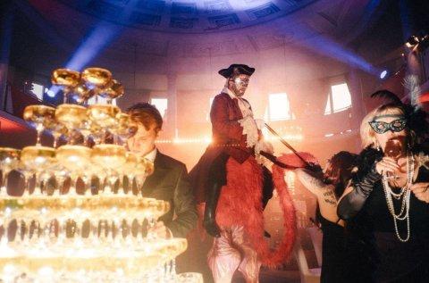 Im Vordergrund ist eine Pyramide aus Champagner-Gläsern. Ein Darsteller sitzt auf einem Flamingo