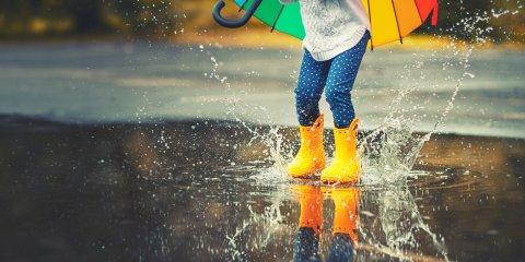 bunt gekleidete Beine springen mit gelben Gummistiefel in eine Pfütze.