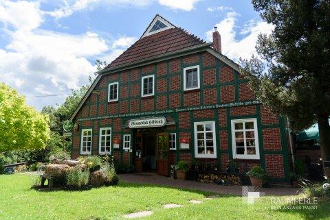 Außenansicht des alten Bauernhaus mit Grünfläche davor.