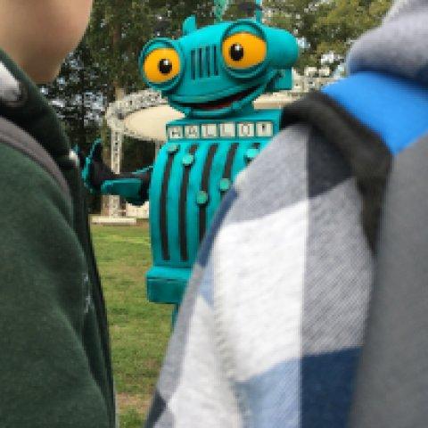 Kinder stehen vor einem Menschen im Kassenkostüm