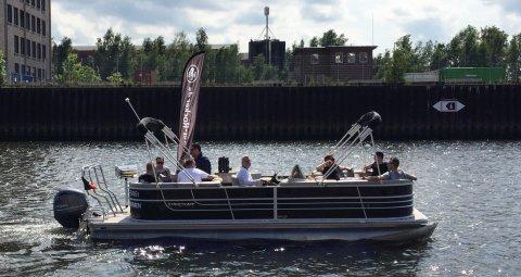Eine Gruppe von Männern sitzt bei Sonne in einem Boot, dass über die Weser schippert.