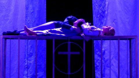 Romeo und Julia liegen auf einem Käfig. Julia hält eine Flasche in der Hand.