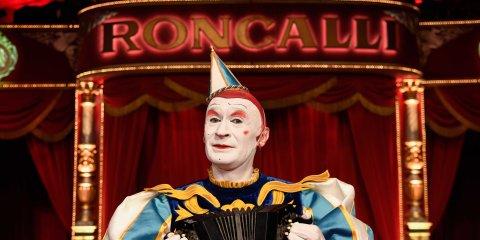 """Ein Clown in einer Manage, im Hintergrund der Schriftzug """"Roncalli"""""""